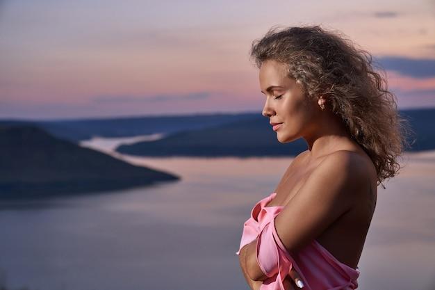 Piękna seksowna dziewczyna pozuje w pobliżu wieczornego jeziora