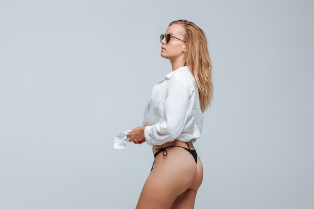 Piękna seksowna dziewczyna w białej koszuli i okularach przeciwsłonecznych w czarnym bikini na jasnoszarym tle