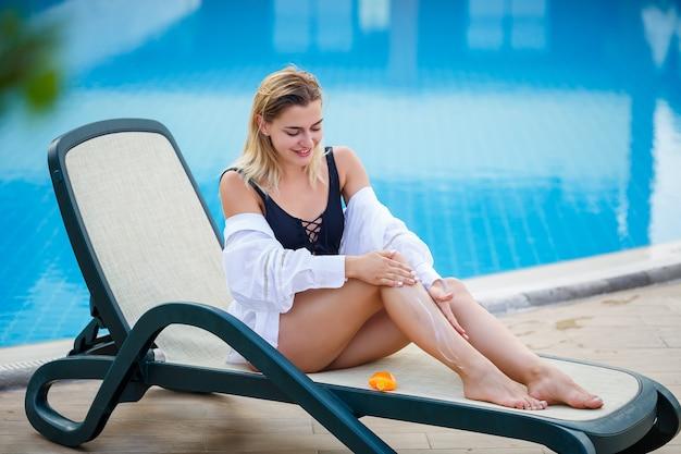 Piękna seksowna dziewczyna w czarnym stroju kąpielowym siedzi przy basenie i nakłada krem przeciwsłoneczny na swoje ciało