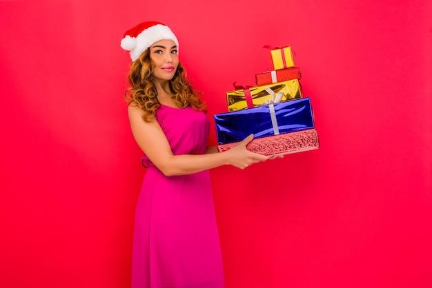 Piękna seksowna dziewczyna w noworocznym kapeluszu, trzymaj w rękach prezenty na czerwonej przestrzeni. obchody bożego narodzenia lub nowego roku