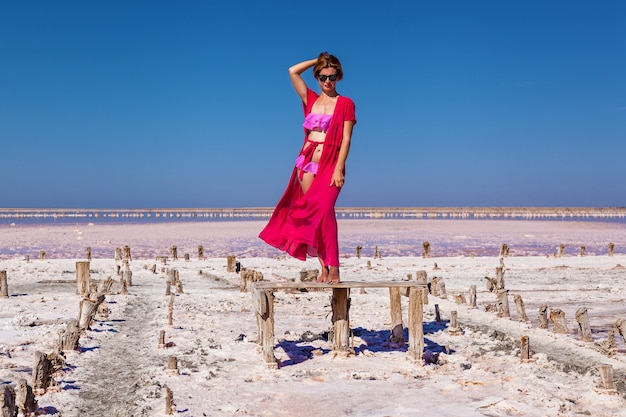 Piękna seksowna dziewczyna w różowym kostiumie kąpielowym pozuje na różowym słonym jeziorze p