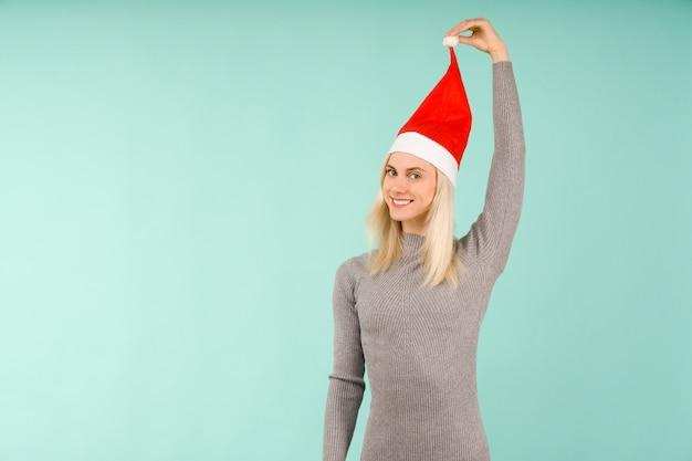 Piękna seksowna dziewczyna w szarej sukience trzymać w ręku nowy rok kapelusz obchody bożego narodzenia lub nowego roku na niebieskim tle