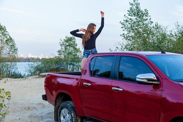 Piękna seksowna dziewczyna z długimi włosami w krótkie jeansowe szorty i czarne body pozowanie w otwartym ciele czerwonego pickupa. dziewczyna pozuje w pobliżu samochodu