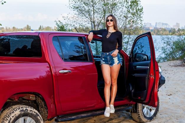 Piękna seksowna dziewczyna z długimi włosami w krótkie jeansowe szorty i czarne body pozowanie w pobliżu otwartych drzwi czerwonego pickupa. dziewczyna pozuje w pobliżu samochodu