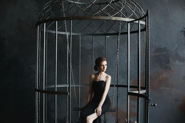 Piękna, seksowna i modna modelka w czarnej sukience pozuje w gigantycznej klatce dla ptaków