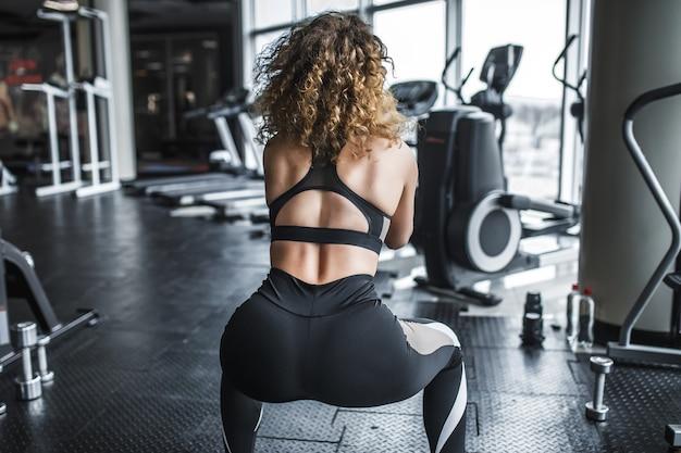 Piękna seksowna kaukaska kobieta z idealną sylwetką pozuje stojąc plecami przy oknie na siłowni obok symulatora wioślarstwa i przysiadów
