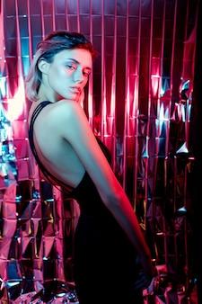 Piękna seksowna kobieta sztuki mody na błyszczącym czerwonym neonowym tle, kolorowe pasemka na twarzy dziewczyny jasne światło