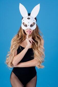 Piękna seksowna kobieta w białej masce królika robi gest shh i wygląda bardzo zmysłowo seksowna modelka