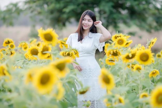 Piękna seksowna kobieta w białej sukni chodzenie na polu słoneczników