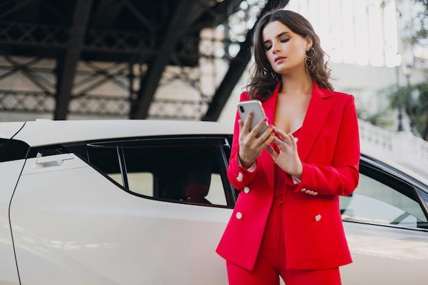 Piękna seksowna kobieta w czerwonym garniturze, pozowanie na samochód, rozmawia na telefon