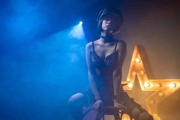 Piękna seksowna kobieta w erotycznej odzieży do dominacji bdsm w promieniach światła i dymu
