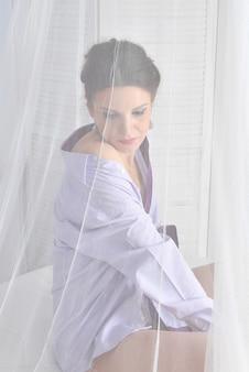 Piękna seksowna kobieta w koszuli i majtki siedzi na białym łóżku.