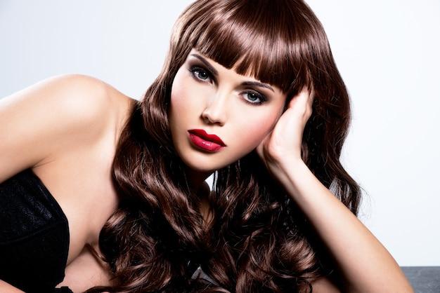 Piękna seksowna kobieta z długimi kręconymi włosami. portret modelki z makijażem mody.