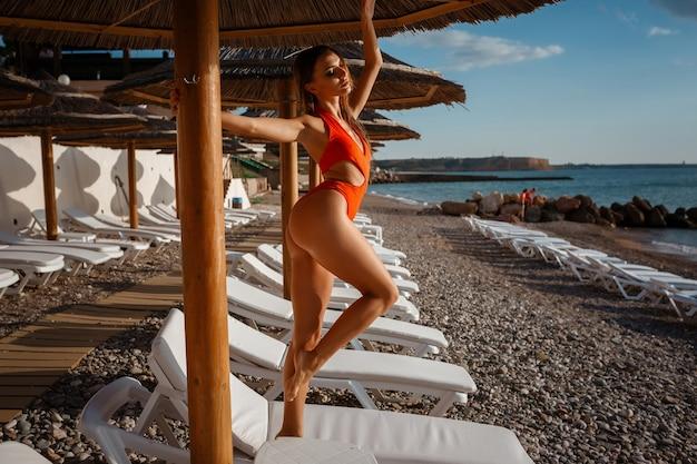 Piękna seksowna młoda kobieta o idealnej szczupłej sylwetce z długimi ciemnymi włosami i mokrym kostiumem kąpielowym w stylowych strojach kąpielowych przed słońcem opalając się przy basenie pływaj opalaj się baw się na plaży