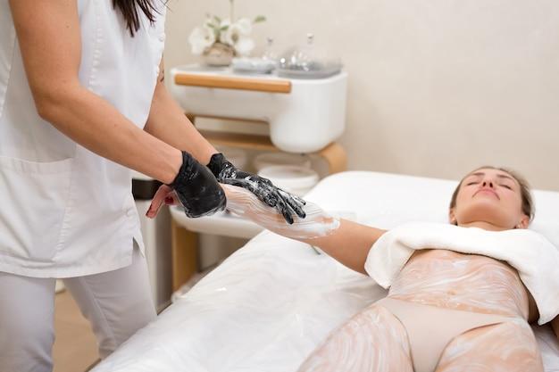 Piękna seksowna młoda kobieta otrzymująca glinkę kosmetyczną, maskę na ciało z alg morskich leżącą na stole do masażu w salonie kosmetycznym. kosmetolog z bliska nakłada na dłoń młodej kobiety maseczkę nawilżającą.