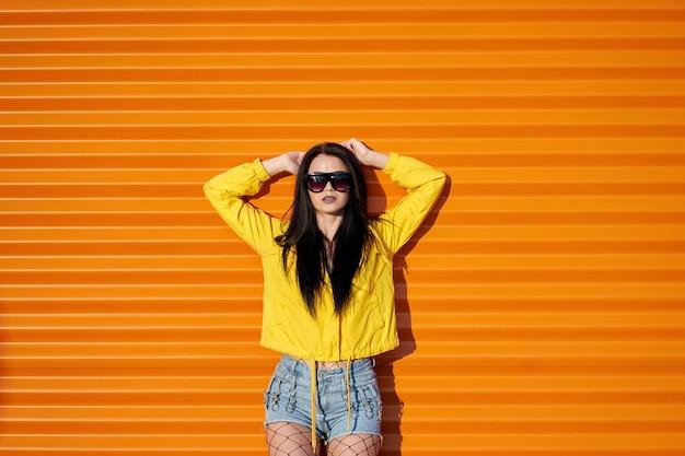 Piękna seksowna młoda stylowa dziewczyna z długimi brunetkami na sobie modną żółtą kurtkę, jeansowe szorty i modne okulary przeciwsłoneczne pozuje na pomarańczowej ścianie miejskiej