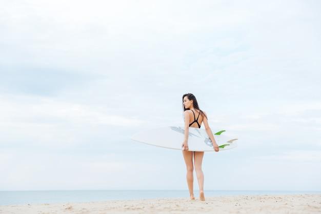 Piękna seksowna młoda surfer dziewczyna spaceru na plaży z deską surfingową