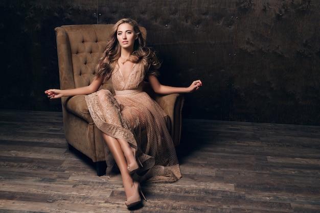 Piękna Seksowna Modelka W Błyszczącej Koronkowej Sukni Wieczorowej, Pozowanie, Siedząc W Fotelu W Kolorze Beżowym Darmowe Zdjęcia