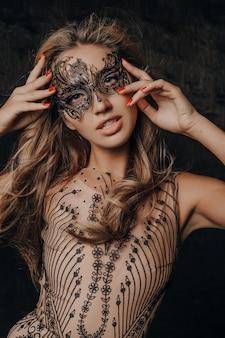 Piękna seksowna modelka w luksusowej koronkowej sukni wieczorowej pozowanie w masce karnawałowej