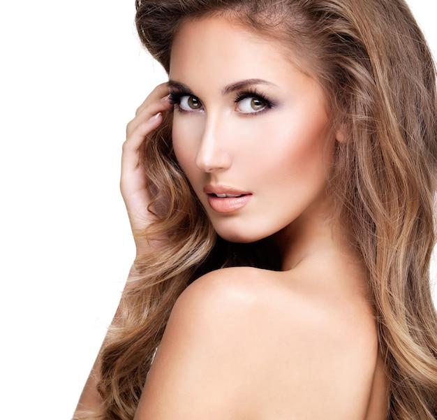 Piękna seksowna modelka z długimi brązowymi włosami dotyka jej ramienia i patrzy na nie. na białym tle