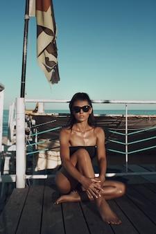 Piękna seksowna niesamowita młoda kobieta w czarnym kostiumie kąpielowym i okularach przeciwsłonecznych pozuje na plaży. długie włosy, czarne bikini, moda, czerwona nić