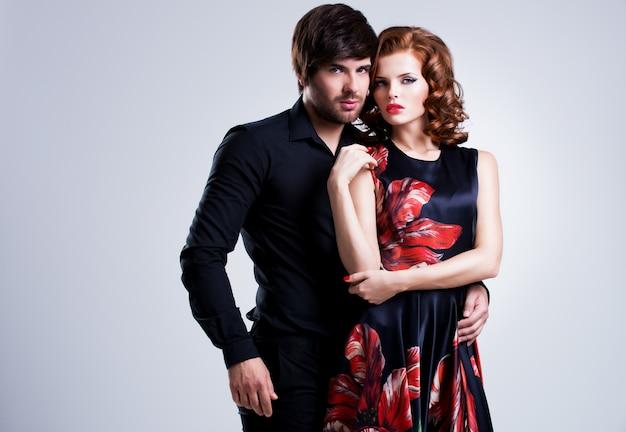 Piękna seksowna para zakochanych stojących na szarym tle.