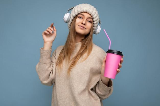 Piękna seksowna pozytywna uśmiechnięta młoda blondynka na sobie beżowy zimowy sweter i kapelusz na białym tle