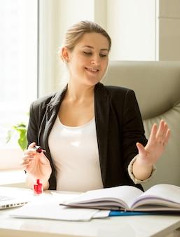 Piękna seksowna sekretarka maluje paznokcie zamiast pracować