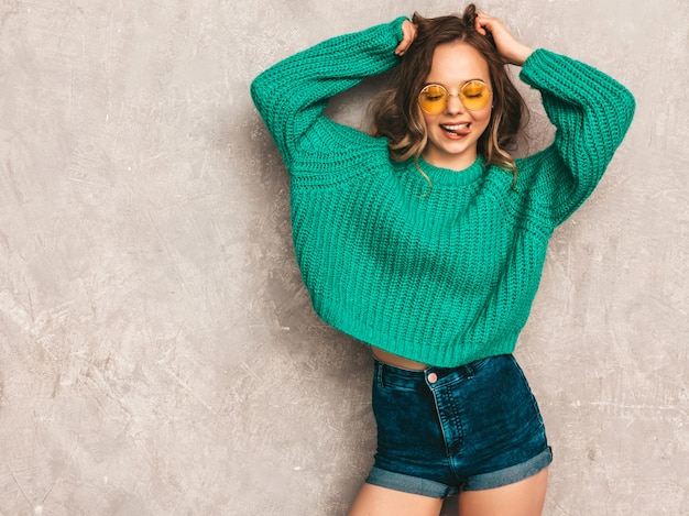 Piękna seksowna uśmiechnięta wspaniała dziewczyna w zielonym modnym swetrze. kobieta stwarzających w okrągłe okulary przeciwsłoneczne. model ma zabawę i pokazuje jej język