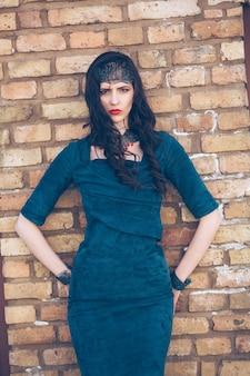 Piękna sexy dziewczyna stylowy makijaż w sukience i ozdoby na tle ściany z cegły