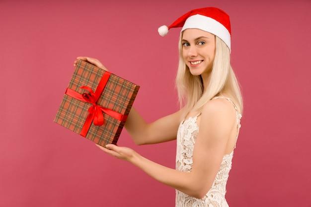 Piękna sexy dziewczyna w noworocznym kapeluszu i białej sukni trzymaj w rękach prezenty