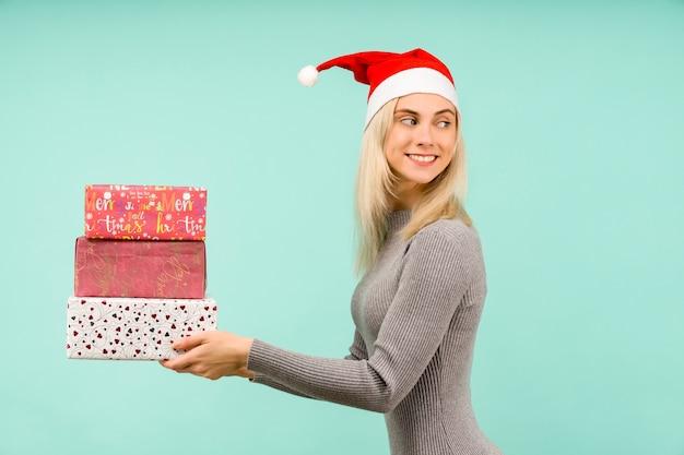 Piękna sexy dziewczyna w noworocznym kapeluszu i szarej sukience, trzymaj w rękach prezenty
