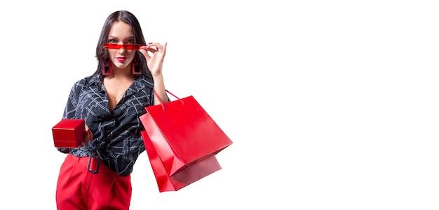 Piękna sexy dziewczyna w okularach z czerwonymi opakowaniami i pudełkiem na biżuterię