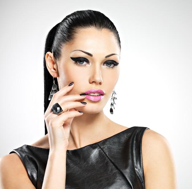 Piękna sexy kobieta moda z czarnymi paznokciami na ładnej twarzy. śliczna modelka ze stylową biżuterią w srebrnym kolorze.