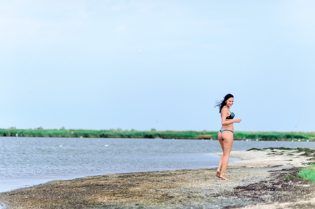 Piękna sexy kobieta odpoczywa nad brzegiem morza