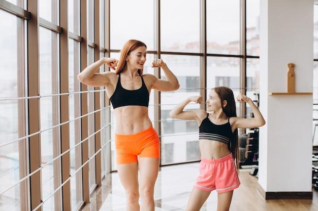 Piękna silna kobieta i urocza córeczka pokazują bicepsy i uśmiechają się podczas ćwiczeń na siłowni