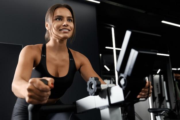Piękna silna kobieta robi trening na rowerze stacjonarnym
