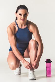 Piękna silna kobieta w odzieży sportowej sznuruje buty