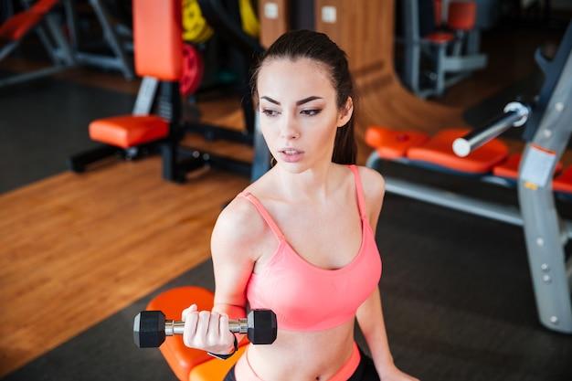 Piękna, silna, młoda kobieta, trenująca sportowiec z hantlami w siłowni