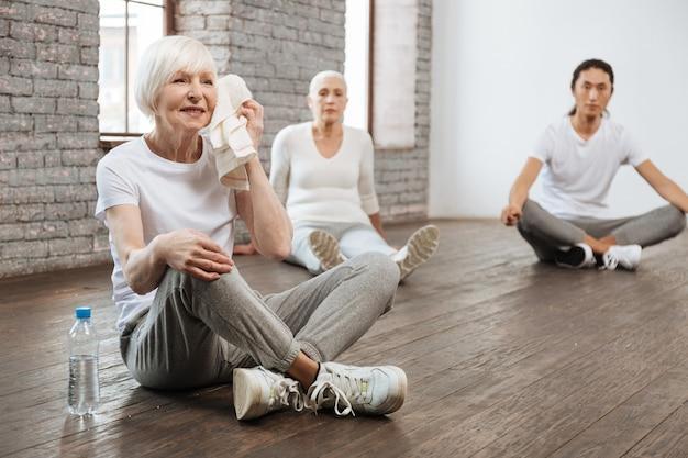 Piękna siwowłosa kobieta ubrana w odzież fitness, trzymając rękę na kolanie podczas przerwy