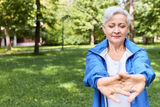 Piękna siwowłosa starsza kobieta w kurtce klejącej pozuje na zewnątrz z zamkniętymi oczami, rozciągając ręce, wykonując ćwiczenia rozgrzewające przed treningiem cardio, miejsce na informacje reklamowe