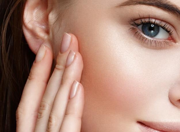 Piękna skóra kobiety zdrowe włosy i uroda oczy rzęsy i usta dotykające palcami jej twarzy. strzał studio.