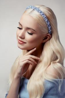 Piękna śliczna blondynka z diademem w niebieskiej sukience