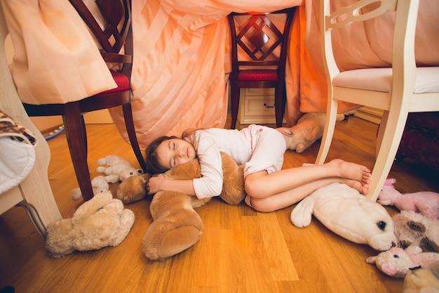 Piękna śliczna dziewczyna śpi na podłodze z zabawkami w sypialni