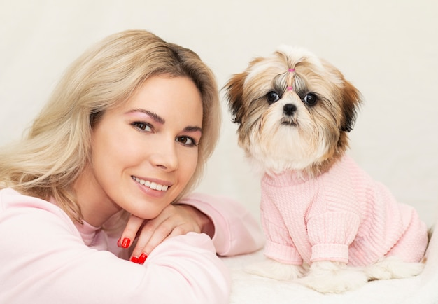 Piękna śliczna dziewczyna trzyma dobrze przygotowanego szczeniaka shih tzu w różowym swetrze