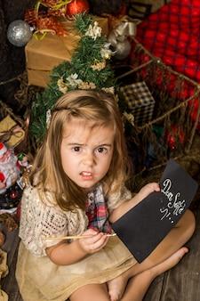 Piękna śliczna mała dziewczynka pisze list do świętego mikołaja w pobliżu świątecznych dekoracji na drewnianej podłodze