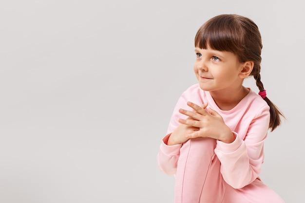 Piękna śliczna mała dziewczynka z zainteresowaniem patrzy w bok