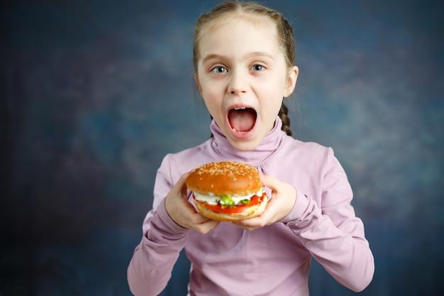Piękna śliczna mała kaukaska blond dziewczyna z hamburgerem