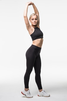 Piękna, śliczna, młoda blondynka wykonuje różne ćwiczenia aktobatyczne rozciągające się na rękach i nogach na białym tle
