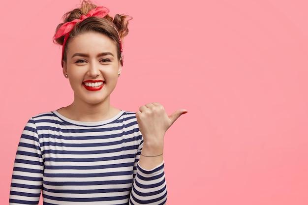 Piękna śliczna młoda kobieta z makijażem, czerwonymi ustami, wskazuje na bok kciukiem, ma lśniący uśmiech, pokazuje puste miejsce